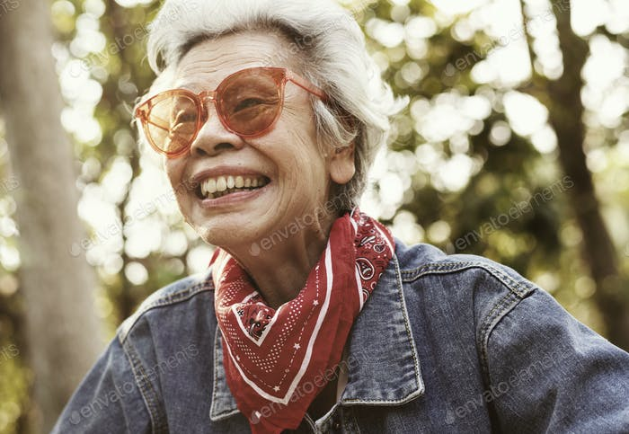 A cheerful female elderly in denim jacket