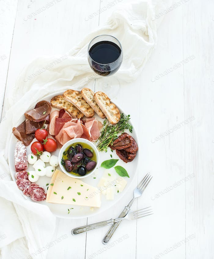 Wine appetizer set. Cherry-tomatoes, parmesan cheese, meat variety, bread slices, dried tomatoes