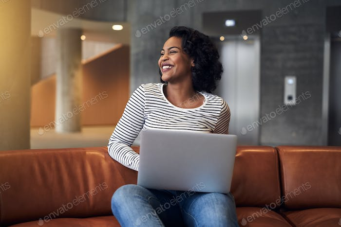 Smiling African college student sitting on a campus couch studying