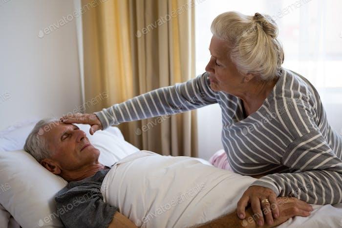 Senior woman sitting by husband sleeping on bed