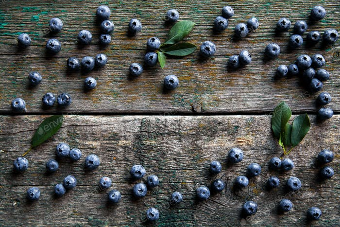 Blueberries on vintage wooden background top view, healthy food on dark table mockup, berry