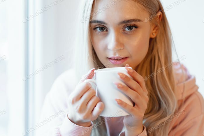 An elf alike, young girl enjoying a cup of coffee or milk while sitting by the window indoors