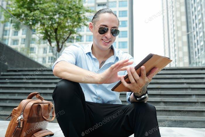 Cheerful man using app on tablet