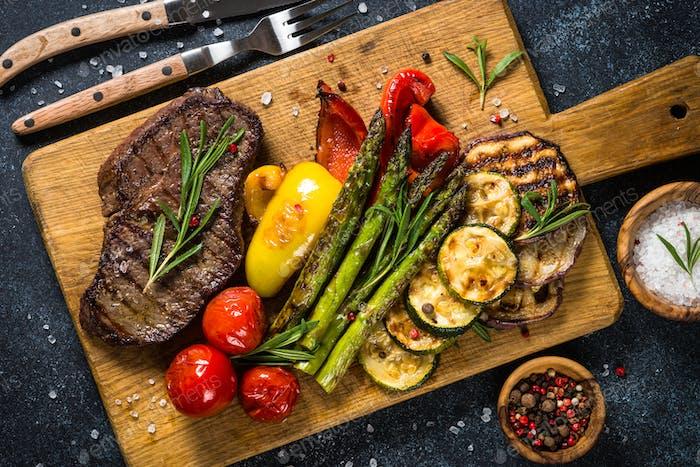 Rindersteak gegrillt mit Gemüse auf schwarzem Steintisch