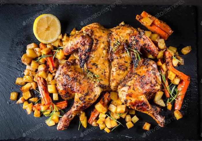 Жареная на бабочке целая курица с жареными овощами и картофелем