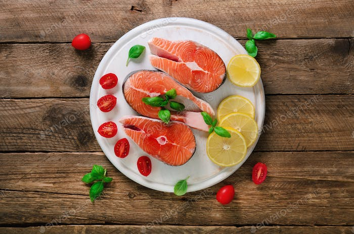 Salmon steaks with lemon, herbs, spices cherry tomatoes on wooden background. Healthy diet food