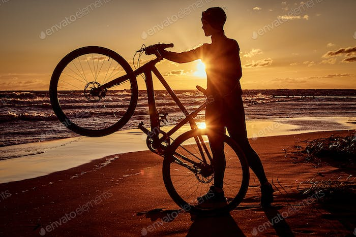 Silhouette of a woman holds a bicycle on a sea coast on a sunset background.