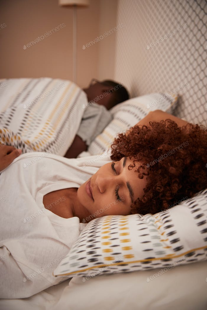 Millennial African American woman lying asleep in bed, her partner in the background, vertical