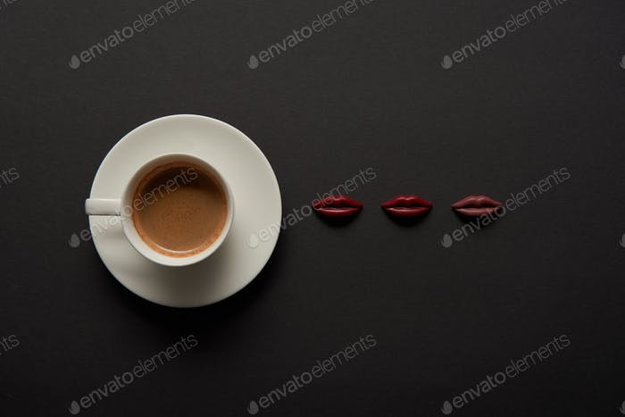 top view of cup of coffee near chocolate lips on black background