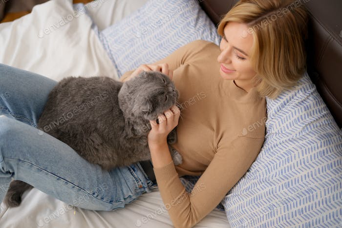 Young woman and cat on bed in the room