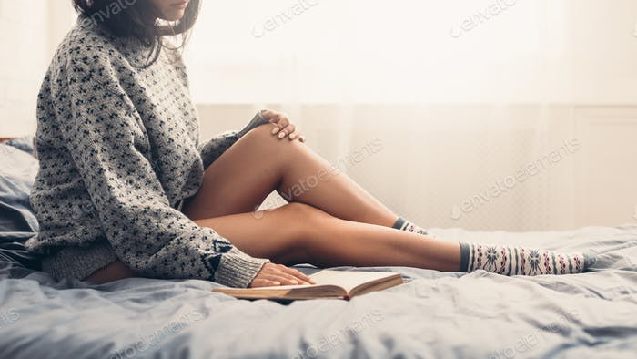 Woman in bed with book and cup of coffee