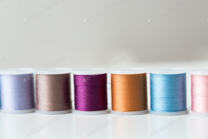 row of colorful thread spools on table