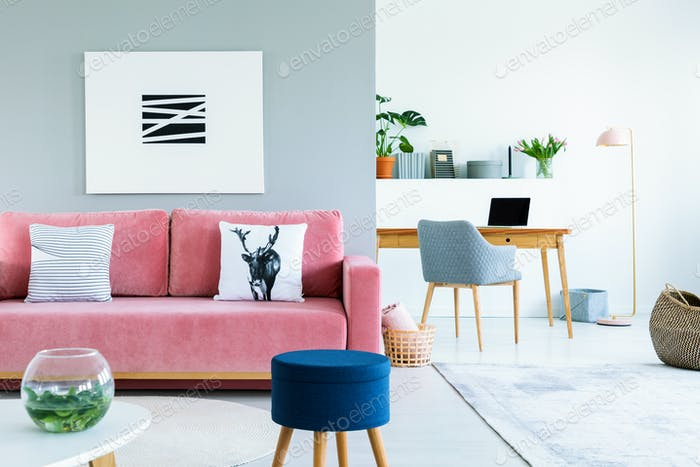 Painting above pink sofa with pillows in open space interior wit