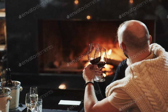 Bald guy with glass of champagne feels satisfaction sitting near the fireplace in the restaurant