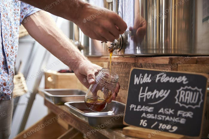 Man Filling Container With Wild Honey In Sustainable Plastic Free Grocery Store