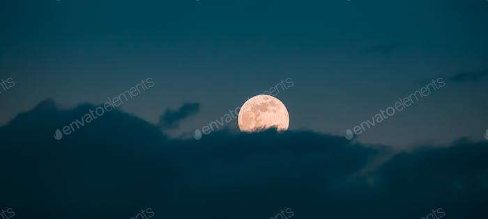 Full Moon Rising In Cloudy Evening Sky