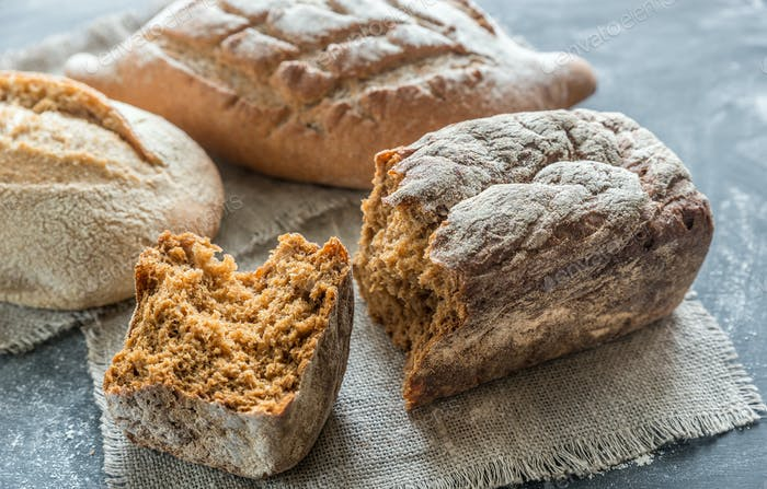 Whole grain breads on the dark wooden background