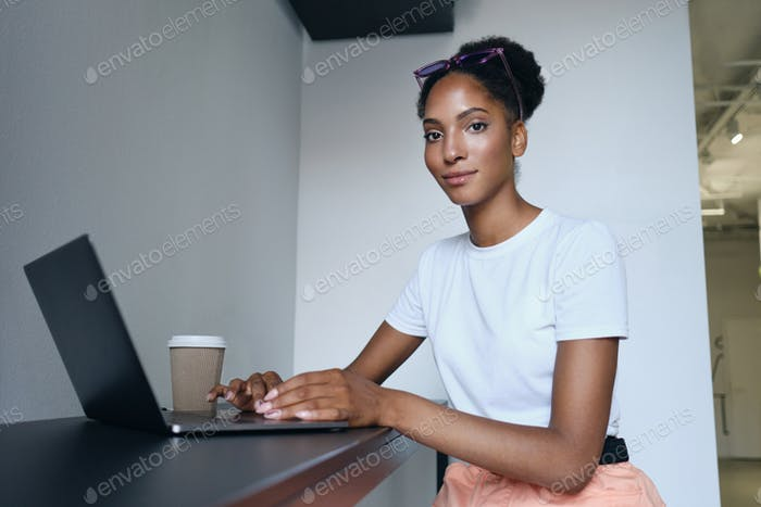 Attractive African American girl working on laptop with coffee to go confidently looking in camera