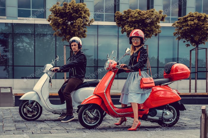 Male and female having fun on moto scooters.