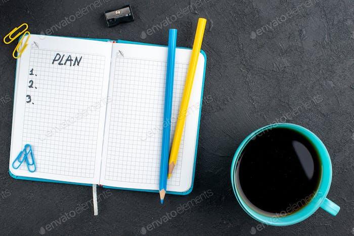 вид сверху чашка чая план, написанный на ноутбуке желтый и синий карандаши точилка для карандашей драгоценные камни клипы на