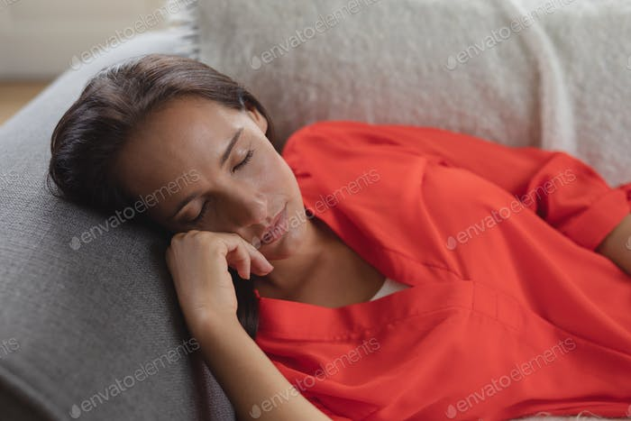 Front view of beautiful Caucasian woman sleeping on a sofa in living room at home