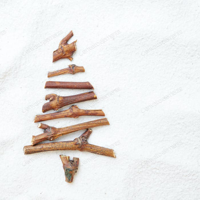 Flat lay stylized Christmas tree made of small twigs on snow bac