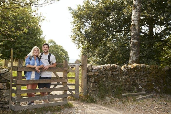 Portrait Of Couple Hiking In Lake District UK Looking Over Wooden Gate
