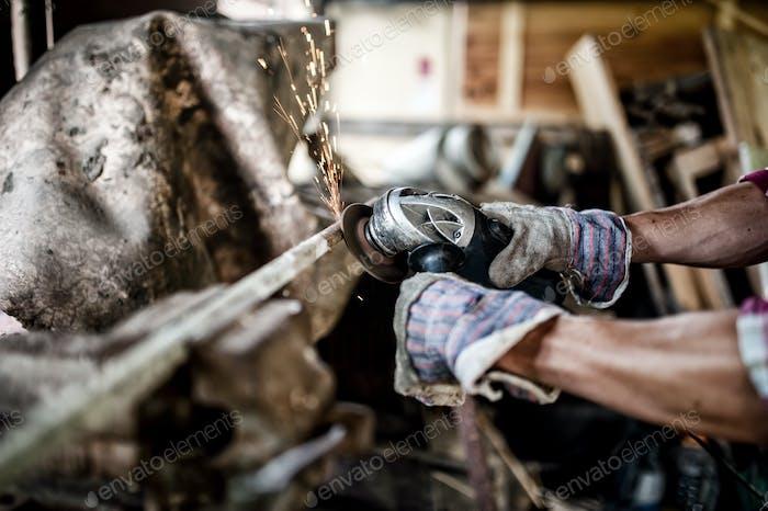 Arbeiter Polieren und Schneiden von Metall mit Winkelschleifer, Leistung auch
