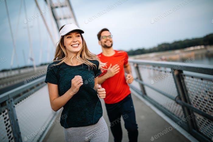 Frühmorgendliches Training. Glückliches Paar läuft über die Brücke