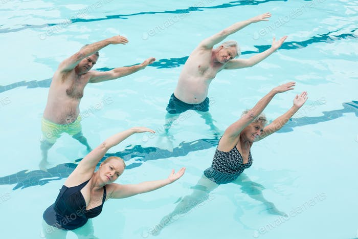 Active seniors exercising in swimming pool
