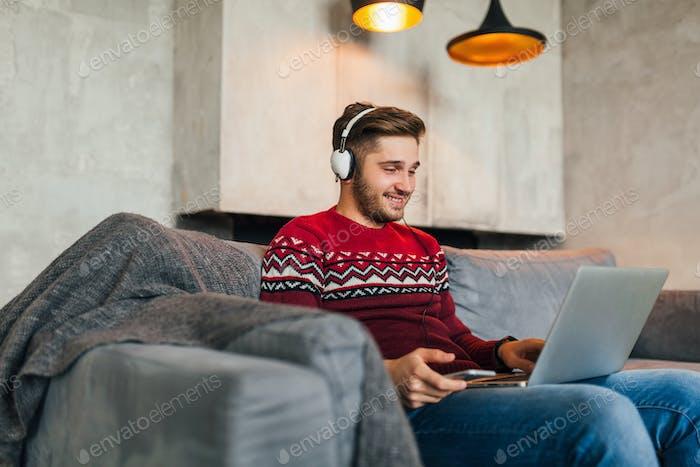 joven atractiva sonriente hombre en el sofá en casa