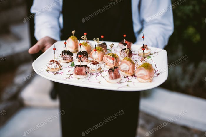 Waiter holding plate with canapés