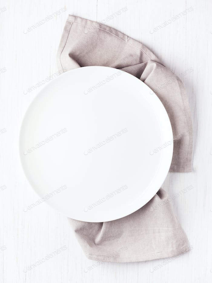 Empty Plate on Linen Napkin on White Table.