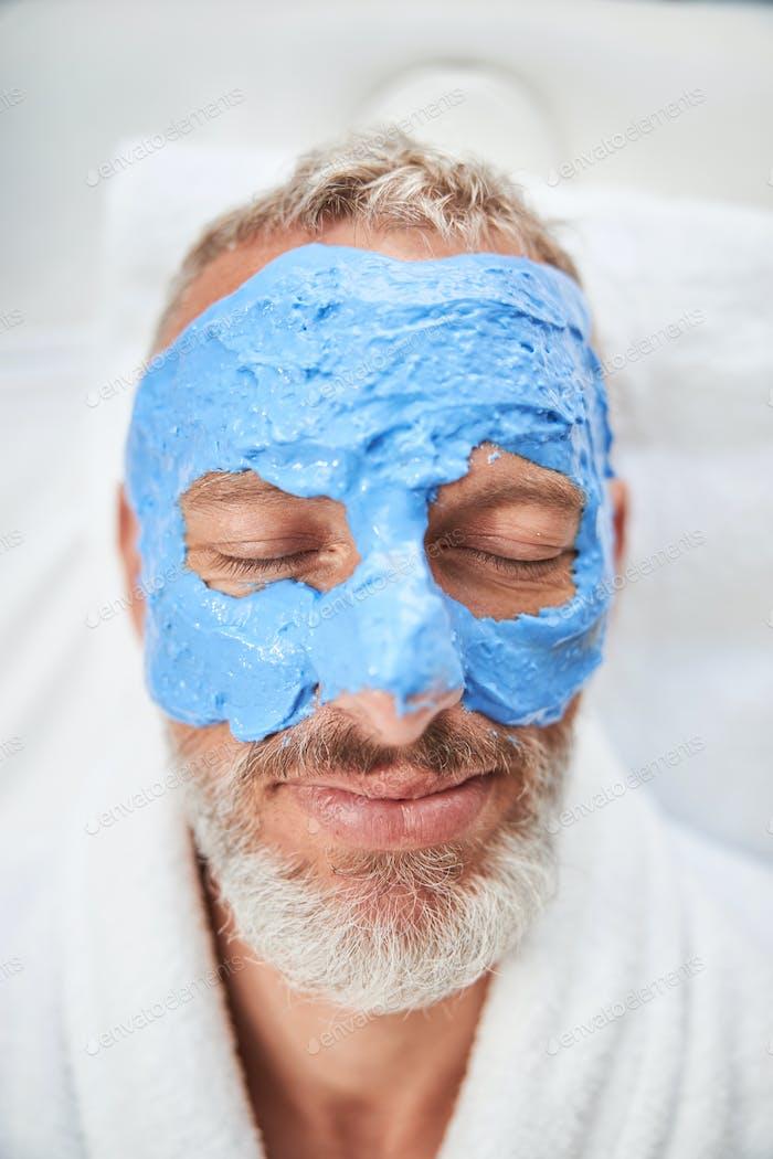 Senior citizen having a moisturizing facial mask