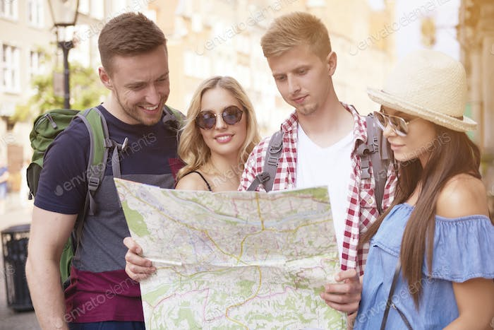 Friends using map while sightseeing