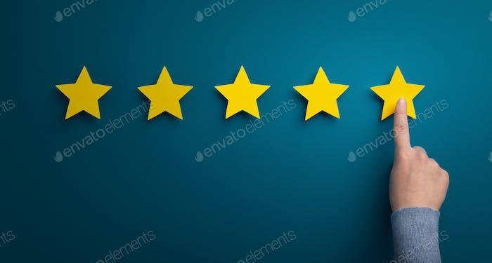 Frau Hand Punkt auf Fünf-Sterne-Bewertung auf grünem Hintergrund