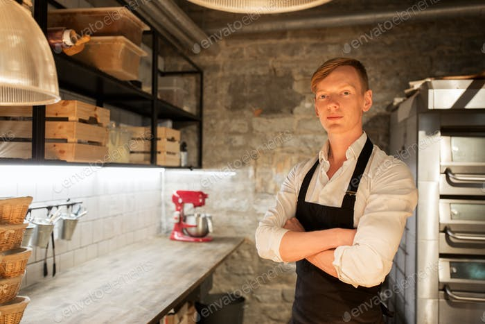 chef or baker in apron at bakery kitchen