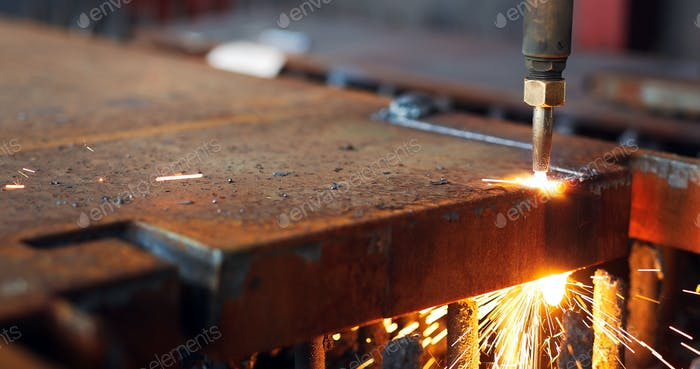 Oxygen torch cuts steel sheet. CNC gas cutting machine. Bright sparks