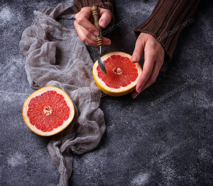Woman hands holding a half of grapefruits
