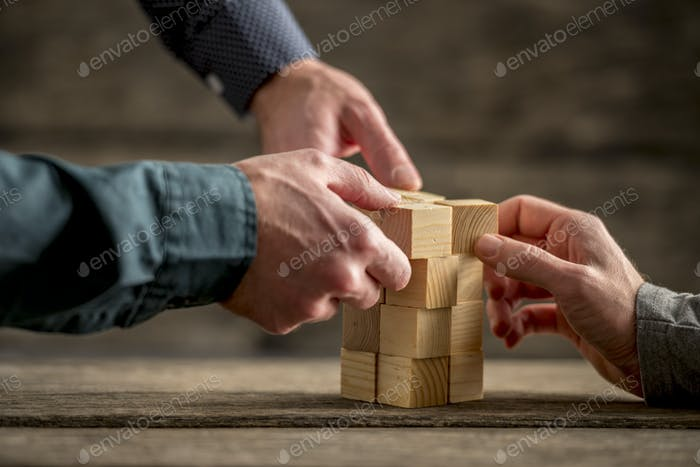 Hands building a tower of wood blocks