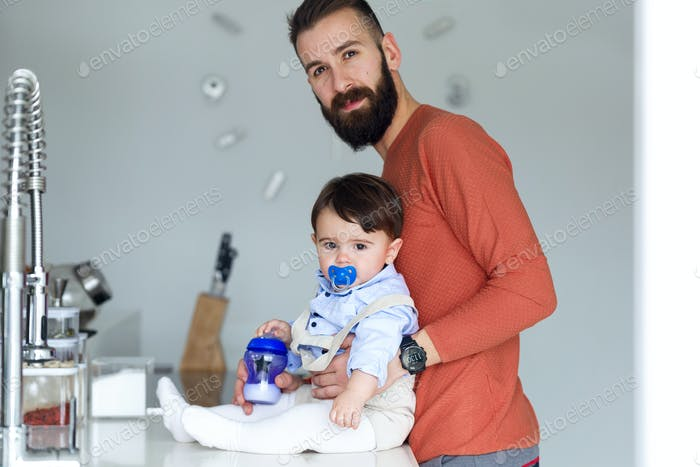 Handsome young father with his baby looking at camera in the kitchen at home.