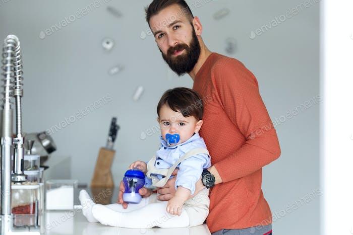 Hübscher junger Vater mit seinem Baby schaute auf die Kamera in der Küche zu Hause.
