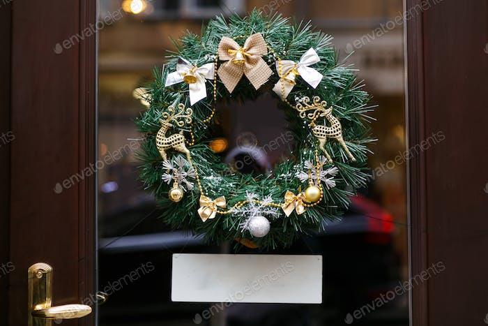 Weihnachtskranz mit goldener Schleife und Rentieren, modernes Dekor auf Schaufenster mit leerem Banner