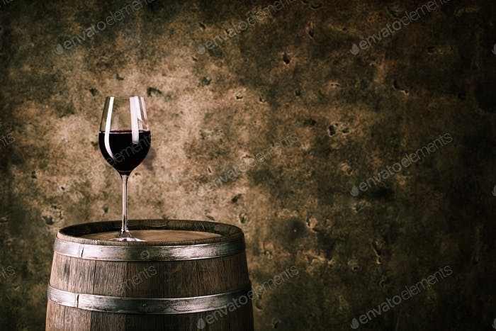 Glass of red wine on wine barrel