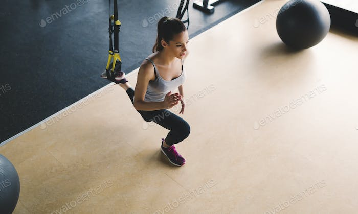 Woman exercising in gym with stretching bands
