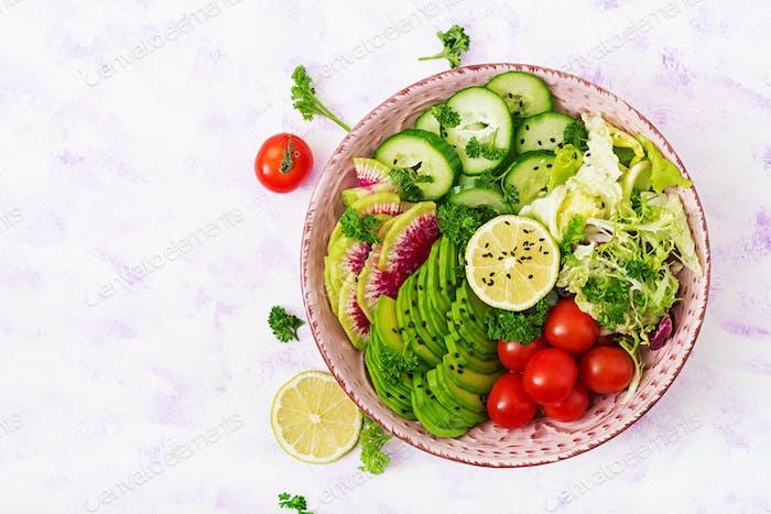 Vegan salad of fresh vegetables - tomatoes, cucumber, watermelon radish and avocado on bowl.