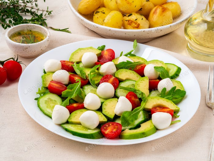 Fresh salad with tomatoes cucumbers arugula mozzarella and avocado. Oil with spices,