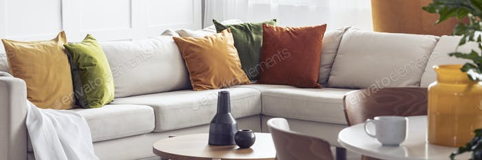 Panorama of yellow and green pillows on beige corner settee in l