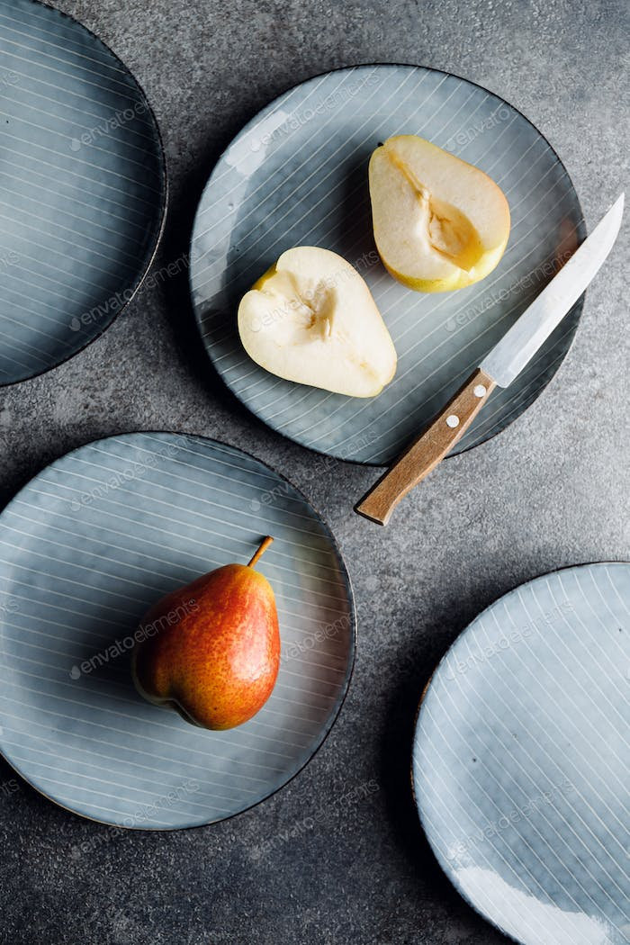Blue food ceramic set with plates and pears over grey textured background.