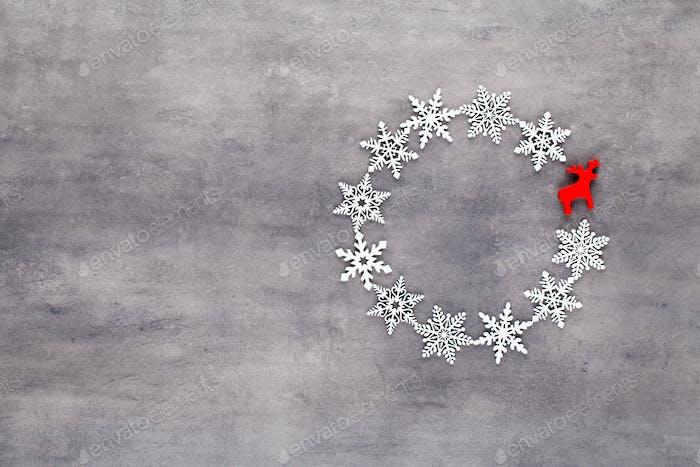 Weiße Schneeflocken Kranz Dekorationen auf grauem Hintergrund.